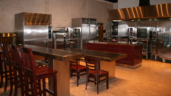 Demo commercial kitchen with wooden chairs/high chairs, stainless steel tables, kitchen counter and stainless steel commercial appliances